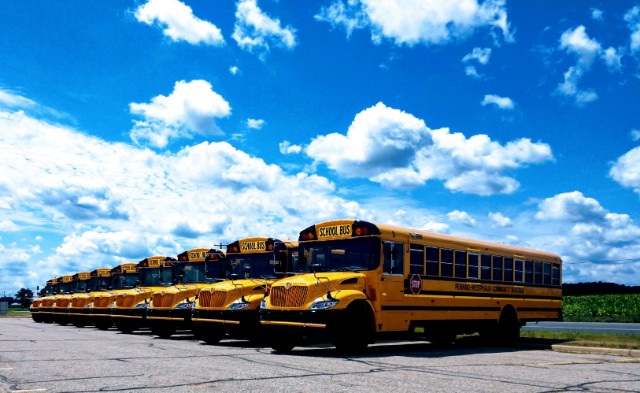 Yellow school buses with blue sky and clouds